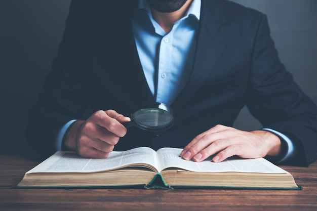 Man hand magnifier with book