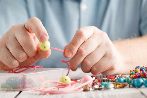 Человек рука делает серьги из полимерной глины.