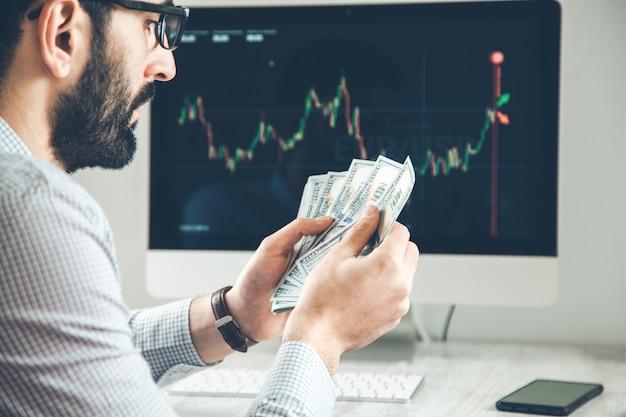 Человек руки деньги с торговым фоном экрана компьютера