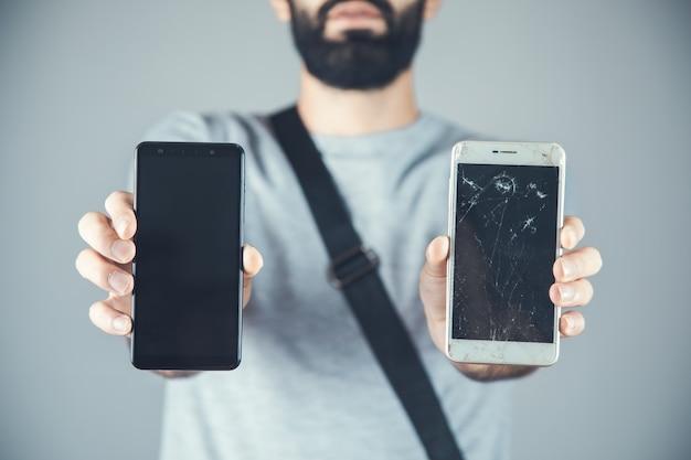 Человек рука новый и сломанный телефон на сером