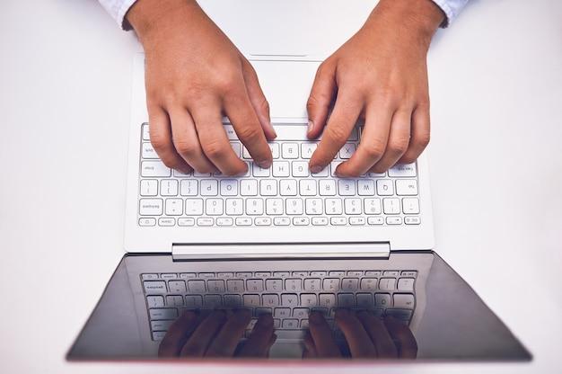 空白の画面モニターとノートパソコンのキーボードの男の手