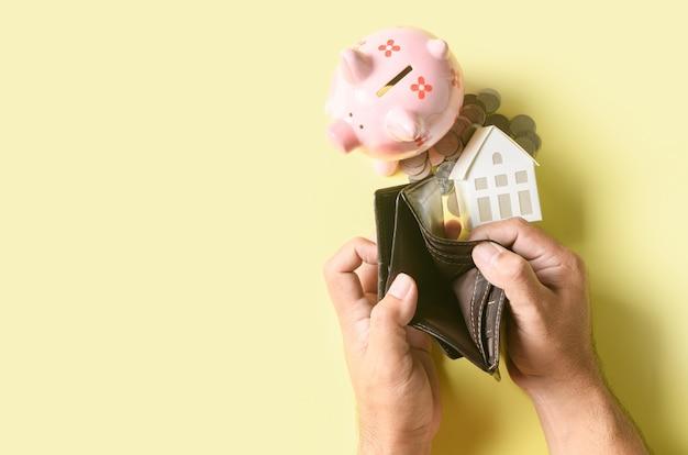 Man hand open an empty wallet with piggy bank