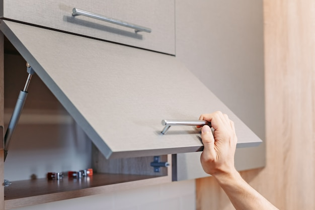 Man hand open kitchen cupboard with handle