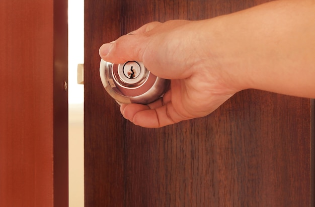 Man hand opening brown wooden door with metal handle