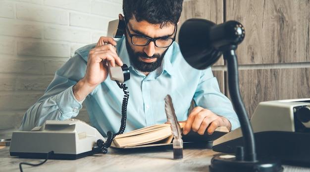 机の上の本と男の携帯電話