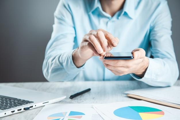 机の上の文書と男の携帯電話