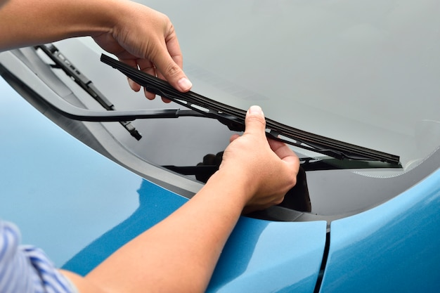 Man hand picking up windscreen wiper