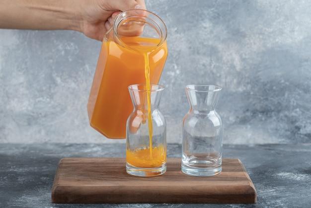 大理石のテーブルの上のガラスにオレンジジュースを注ぐ人の手。