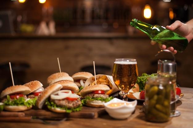 남자 손은 빈티지 테이블에 서 있는 유리에 더 큰 맥주를 붓습니다. 흐릿한 카운터 바. 피클 항아리.