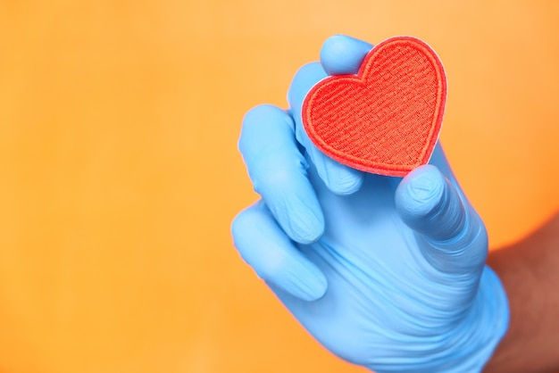 Man hand in protective gloves holding red heart .