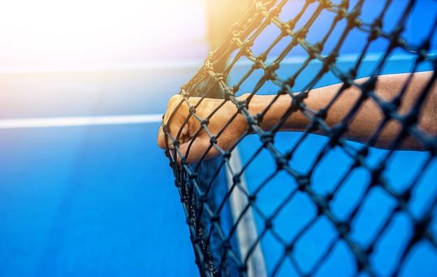 人の手のパンチテニスコート、太陽の光