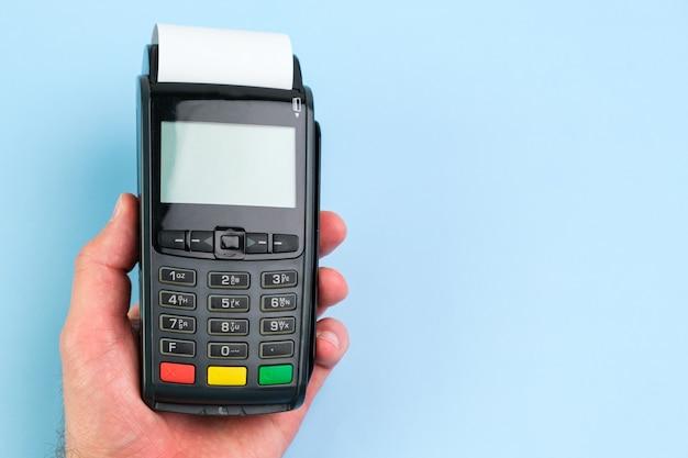 Рука человека, нажимая кнопку на терминале pos с рулонной бумажной лентой на синем фоне