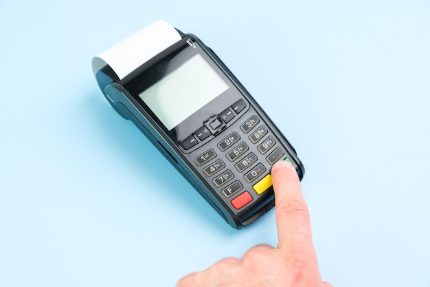 Man hand pushing a button on pos terminal with roll paper cash tape on the blue background