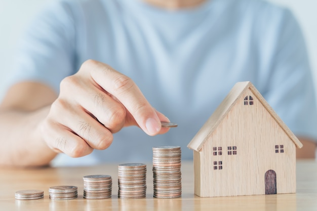 Man hand put coin on coins stack with wooden house on wood table saving money for buying house