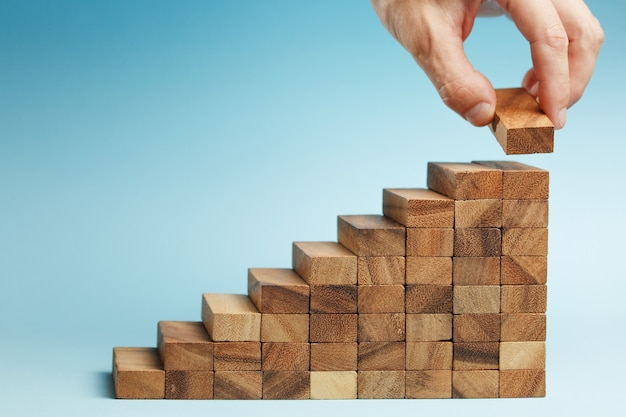 Рука человека положила деревянные блоки, укладывая укладку для развития как ступенчатая лестница на синюю стену. концепция роста и плана успеха.