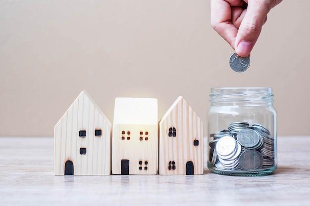 Рука человека, положить монету в стеклянную банку и модель деревянного дома