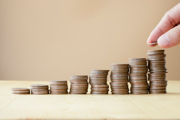 Man hand putting coins stacking for growth business and saving investment concept.