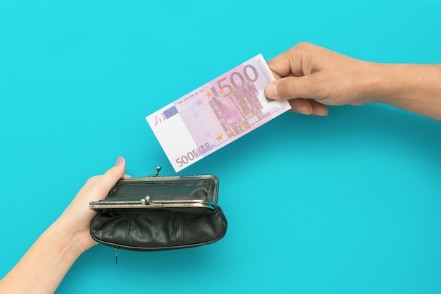 Man hand putting five hundred euro bill in purse in woman hand. financial crisis concept. high quality photo