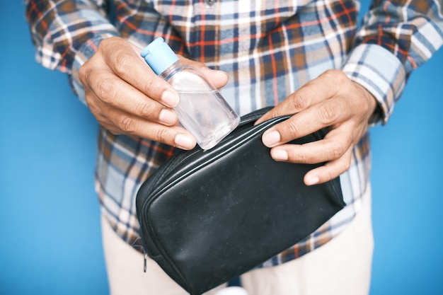 남자 손 작은 가방에 손 소독제를 넣어