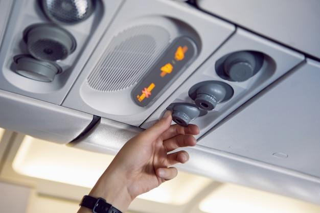 Рука человека регулирует воздух и свет в самолете на приборной панели выше