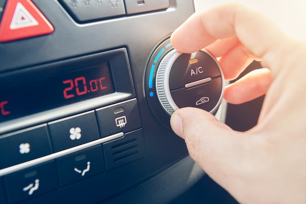 男の手で車内のエアコンの温度を設定しました。車の空調システムをオンにするドライバー。車で旅行します。セレクティブフォーカスでビューをクローズアップ。