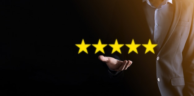Man hand showing on five star excellent rating.pointing five star symbol to increase rating of company.review, increase rating or ranking, evaluation and classification concept.