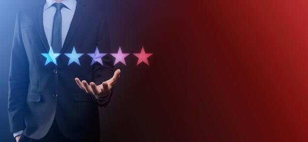 Рука человека, показывающая на пять звезд отличный рейтинг. указывая пятизвездочный символ для повышения рейтинга компании. обзор, повышение рейтинга или ранжирования, оценки и концепции классификации