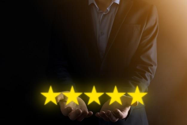 5つ星の優れた評価を示す男の手。会社の評価を上げるために5つ星のシンボルを指す。レビュー、評価またはランク付け、評価および分類の概念を上げる。