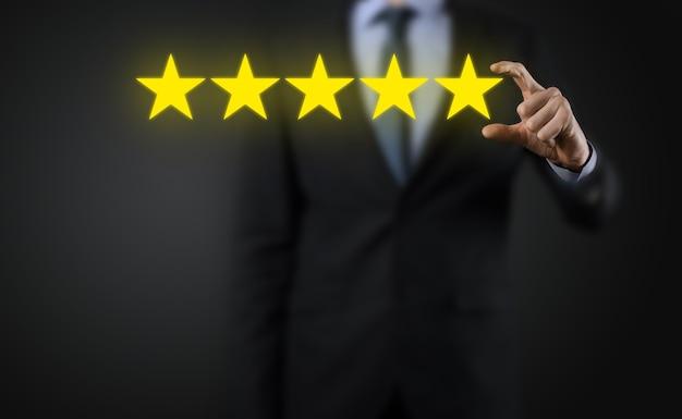 5つ星の優れた評価を示す男の手。会社の評価を上げるために5つ星のシンボルを指しています。レビュー、評価またはランク付け、評価および分類の概念を高めます。