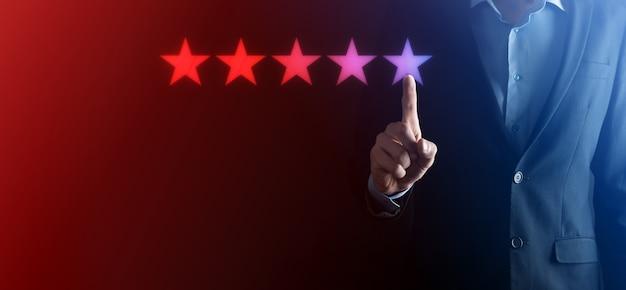 Рука человека, показывающая на пять звезд отличный рейтинг. указывая пятизвездочный символ для повышения рейтинга компании. обзор, повышение рейтинга или ранжирования, оценки и концепции классификации.