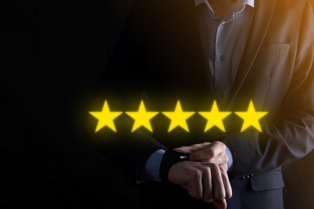 5つ星の優れた評価を示す男の手。会社の評価を上げるために5つ星のシンボルを指しています。