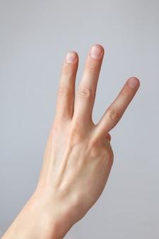 男の手は3番目を示しています。カウントダウンジェスチャーまたはサイン。手話。