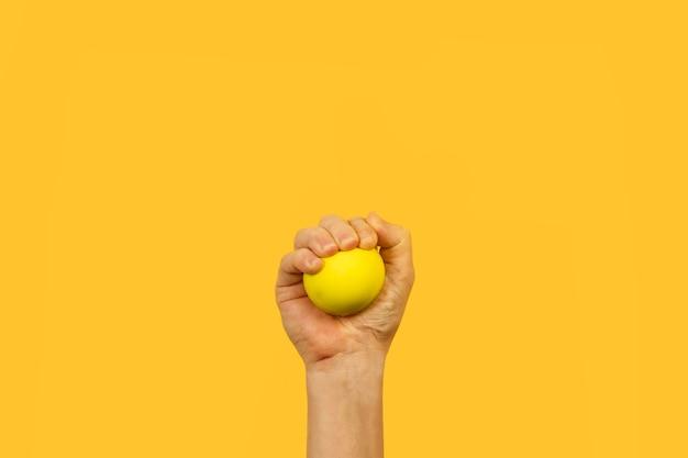 黄色の背景に黄色のストレスボールを握る男の手
