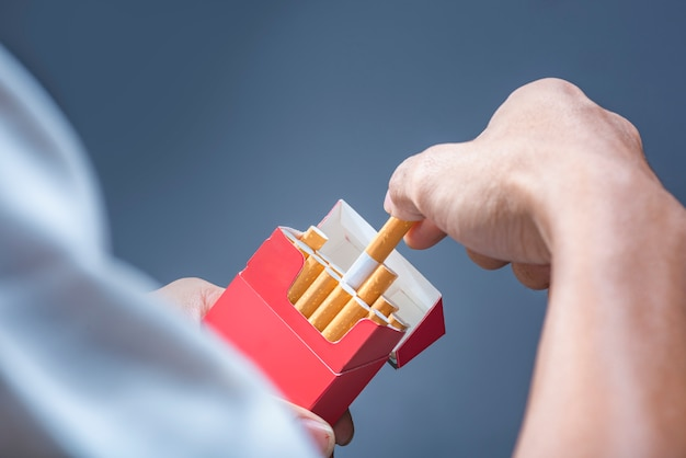 Man hand take a cigarette from red cigarette pack