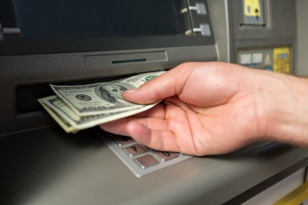 Рука человека принимая долларовые купюры из банкомата