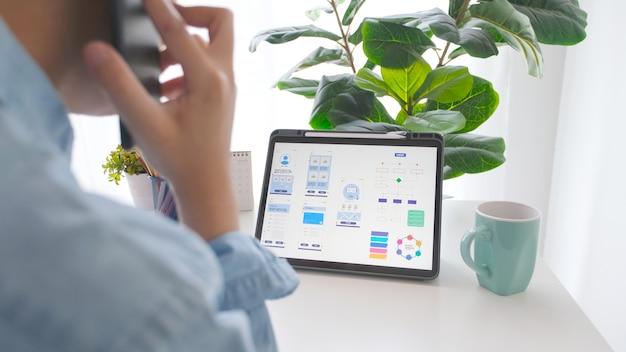 ホームオフィスでモバイルアプリ開発プロトタイプのデジタルタブレットで作業しながら電話を話す男の手