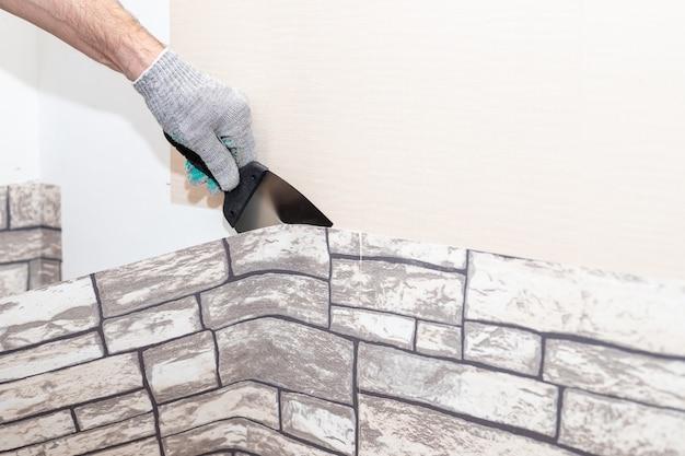 Рука человека оторвать старые светлые обои от стены. подготовка к домашним ремонтным работам. снятие обоев с помощью шпателя, процесс обновления ремонта стены комнаты. копировать пространство