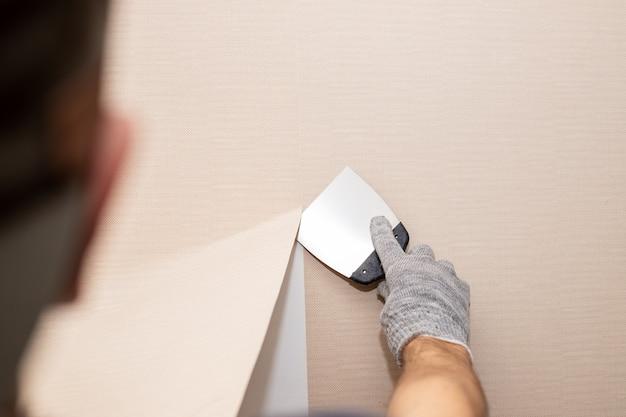남자 손은 벽에서 오래된 빛 벽지를 떼어냅니다. 집 수리 작업을 준비합니다. 주걱으로 벽지 제거, 벽 방 수리를 업데이트하는 과정. 복사 공간