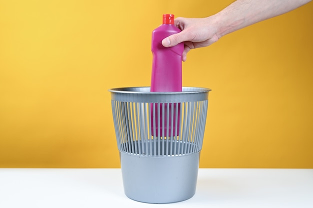 空のプラスチック製の水筒をゴミ箱に投げる男の手