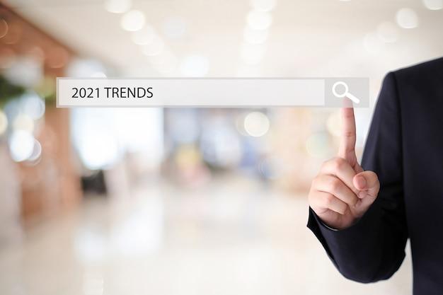 Рука человека, касающаяся бизнес-стратегии 2021 года на панели поиска над размытым офисом