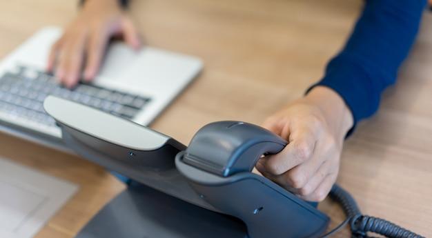 ノートパソコンで働いているハンドセット電話で手を触れている男の手