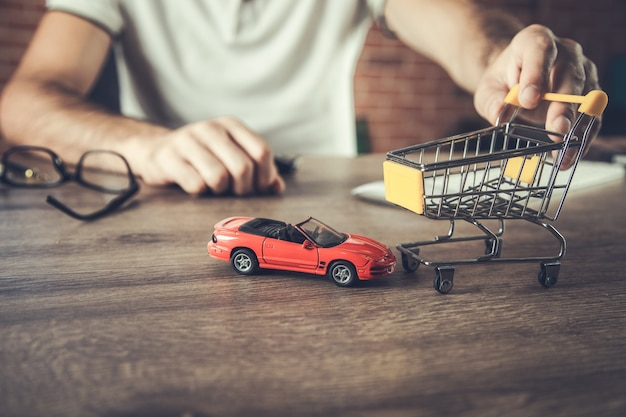 Man hand toy cars and shopping cart