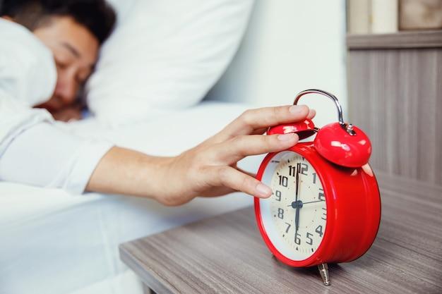 Рука человека выключает красный будильник, просыпаясь утром