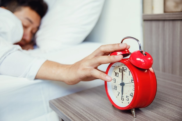 Man hand turning off red alarm clock waking up at morning