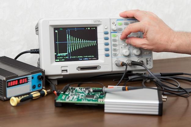 Man hand turning signal adjustment knob on oscilloscope
