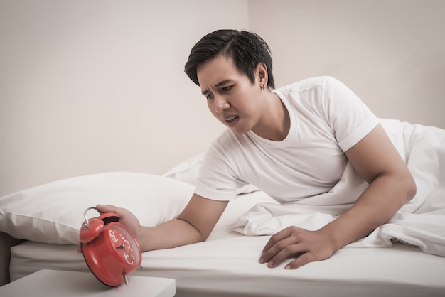 Man hand turns off the alarm clock hurry waking up at morning