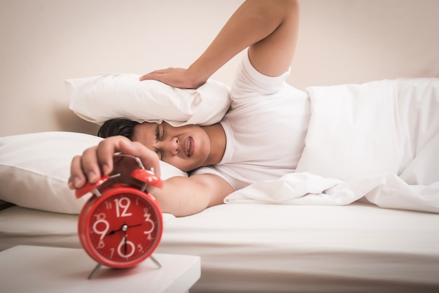 Man hand turns off the alarm clock waking up at morning