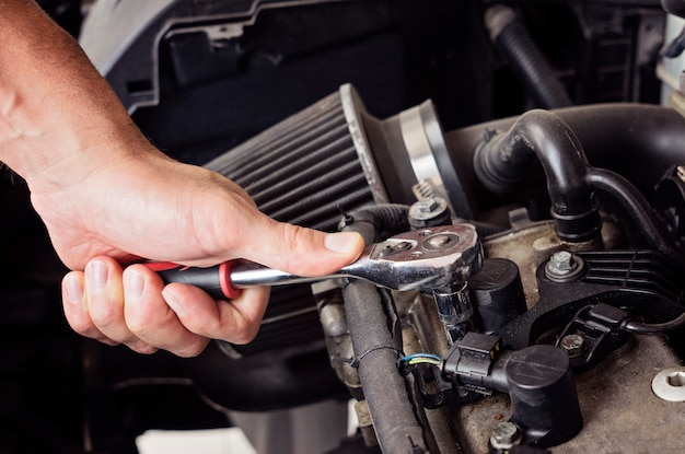 A man hand unscrews the spark plugs