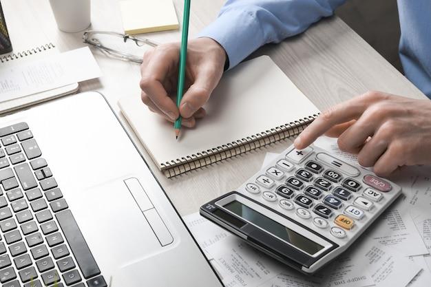 Рука человека с помощью калькулятора и записи делает заметку с расчетом стоимости и налогов в домашнем офисе. бизнесмен делает некоторые документы на рабочем месте
