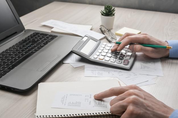 Рука человека с помощью калькулятора и записи делает заметку с расчетом затрат и налогов в домашнем офисе. бизнесмен делает некоторые документы на рабочем месте